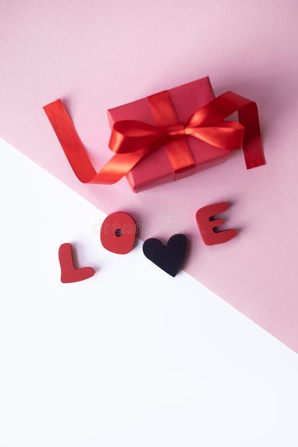 Kleines Geschenk mit rotem Bogen mit Liebeswort auf hellem Hintergrund Freier Platz für Ihren Text stockbilder