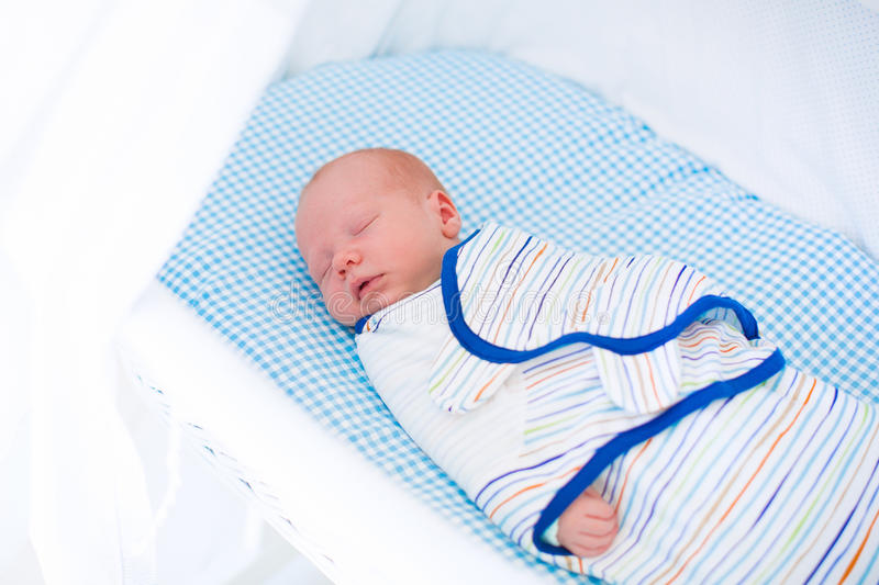 Kleines gewickeltes Baby im weißen Bett stockbild