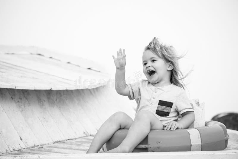 Kleines glückliches Baby, das in der roten Rettungsleine oder im Rettungsring sitzt lizenzfreie stockfotografie