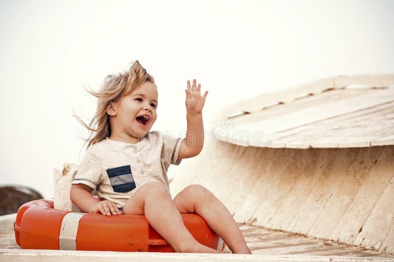 Kleines glückliches Baby, das in der roten Rettungsleine oder im Rettungsring sitzt lizenzfreie stockfotos