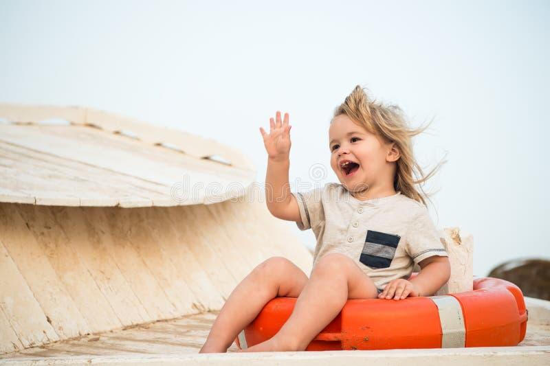 Kleines glückliches Baby, das in der roten Rettungsleine oder im Rettungsring sitzt stockfoto