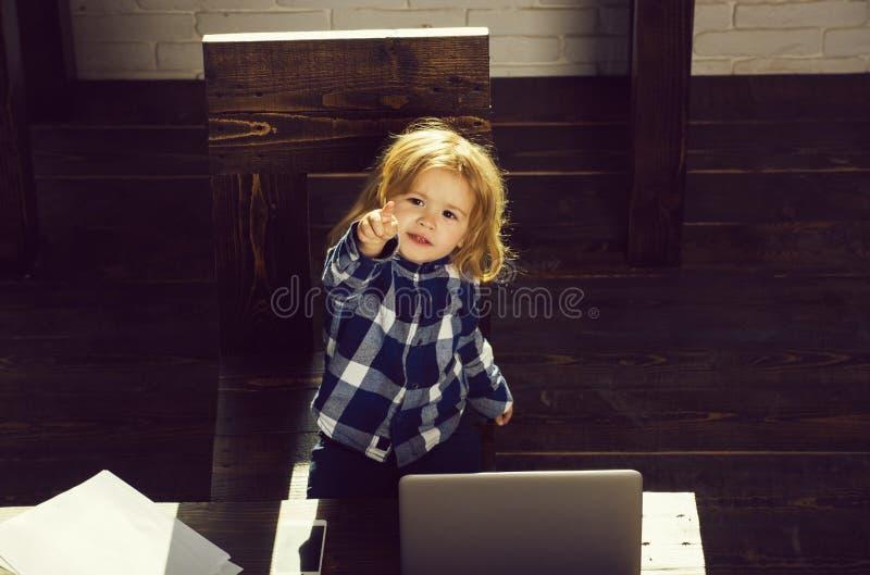 Kleines glückliches Geschäftskind mit Laptop, Handy, Papierblatt stockfotos