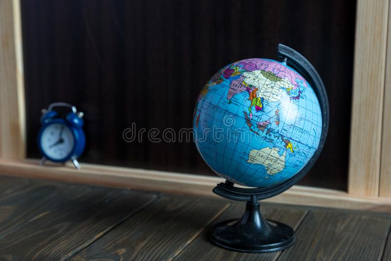 Kleines globus, Uhr und Briefpapier auf dem Holztisch vor Tafel Studienkonzept stockfotos