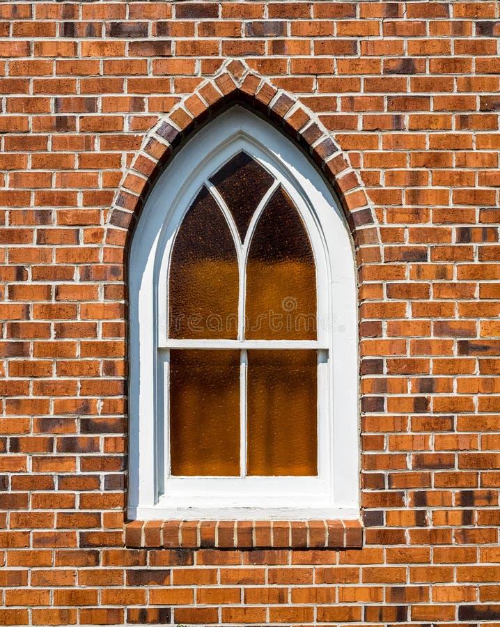 Kleines gotisches Fenster in der Wand des roten Backsteins lizenzfreie stockfotografie