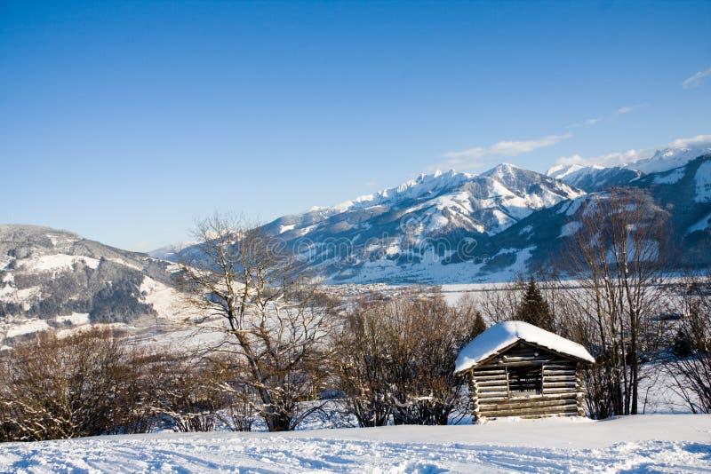 Kleines Häuschen in den Alpen im Winter stockbild