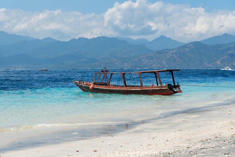 Kleines hölzernes Boot auf blauem Strand mit bewölktem Himmel und Lombok-Insel auf Hintergrund Gili Trawangan, Indonesien stockbild