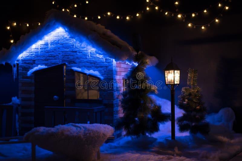 Kleines hölzernes Häuschen wird mit Weihnachtslichtern verziert lizenzfreie stockfotografie