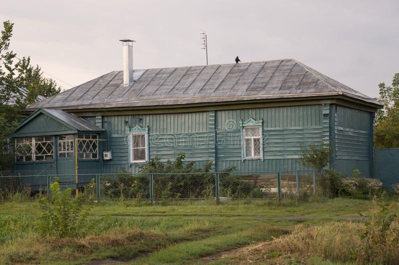 Kleines hölzernes Haus der grünen Farbe im Vorort Grünes Gras und Bäume herum stockbilder
