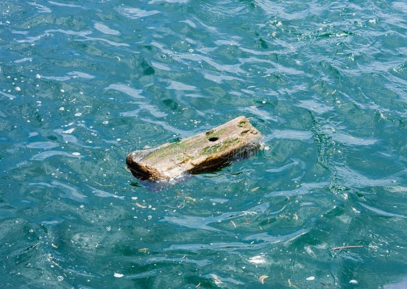 Kleines hölzernes Stück mit dem Loch, das im Wasser treibt stockfoto