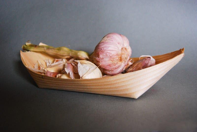 Kleines hölzernes Wiederverwertungsboot, das rosa Knoblauchknollen enthält stockbild