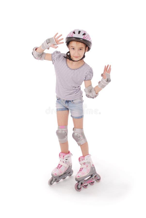 Kleines hübsches Mädchen auf Rollschuhen stockfoto