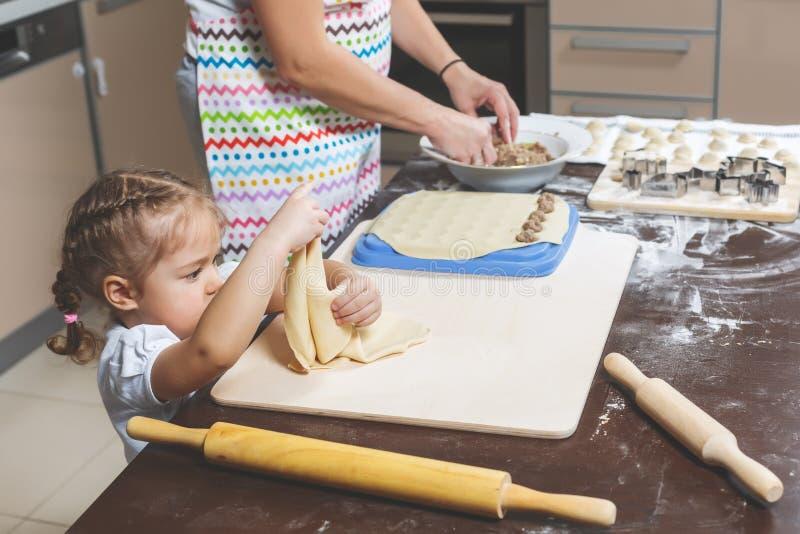 Kleines hübsches Mädchen kocht Teig in der Küche zu Hause, um ihrer Mutter zu helfen, Mehlklöße zu machen stockbilder