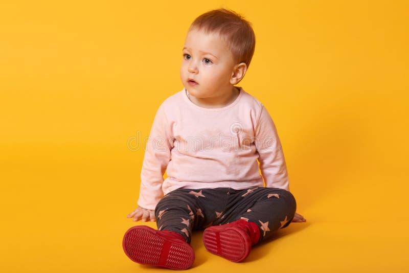 Kleines hübsches Mädchen sitzt auf Boden, gekleidete Strickjacke, Hose mit Sternen und rote Schuhe, schaut beiseite, findet Freun stockfotografie