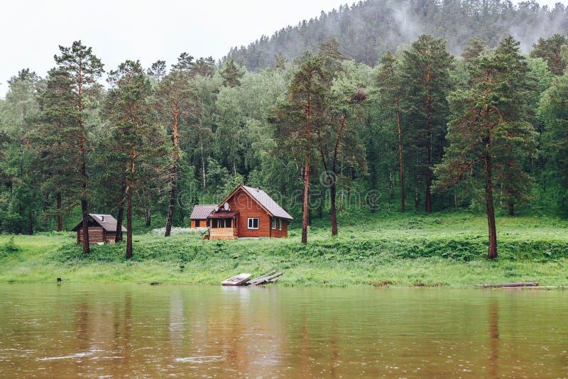Kleines Haus im Wald auf der Flussbank stockbilder
