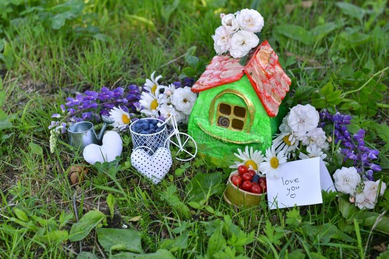 Kleines Haus mit Anmerkungsliebe Sie, Sommerbeeren und Blumen lizenzfreie stockfotografie