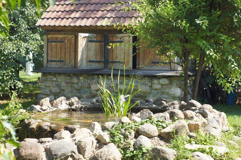 Kleines Haus mit einem Teich im Garten stockfotos