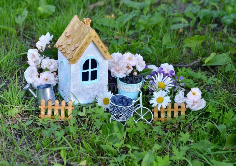 Kleines Haus mit Rosen und Gänseblümchen blüht im Garten stockbild