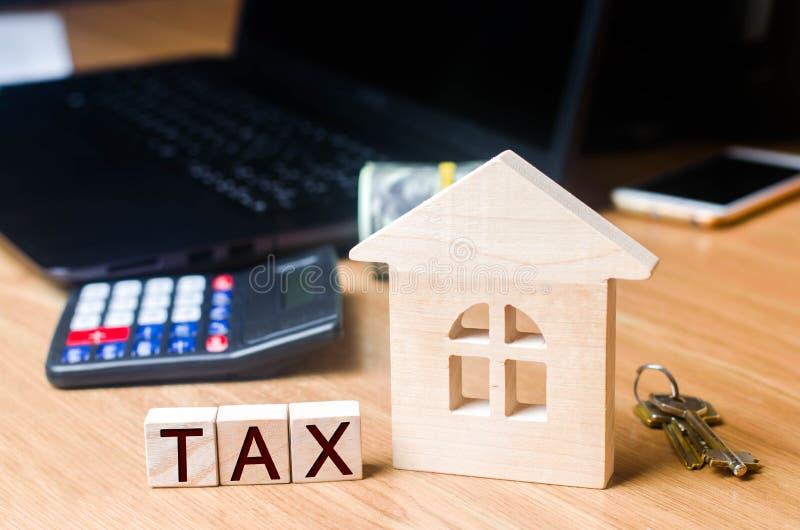 Kleines Holzhaus und Steuern auf dem Desktop Steuern auf Immobilien, Zahlung Strafe, Rückstände Register von Steuerzahlern für Ei lizenzfreies stockbild