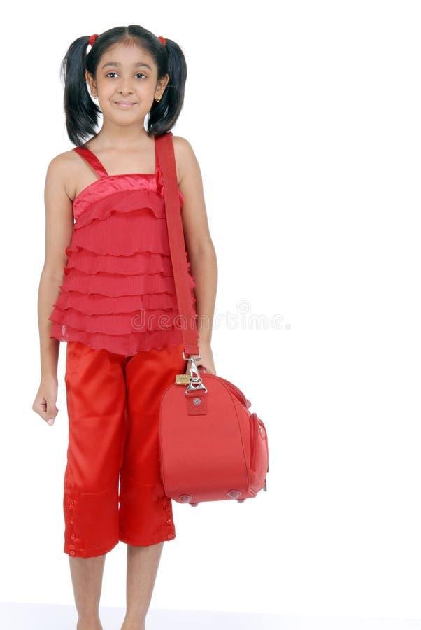 Kleines indisches Mädchen, das mit rotem Beutel steht lizenzfreies stockfoto