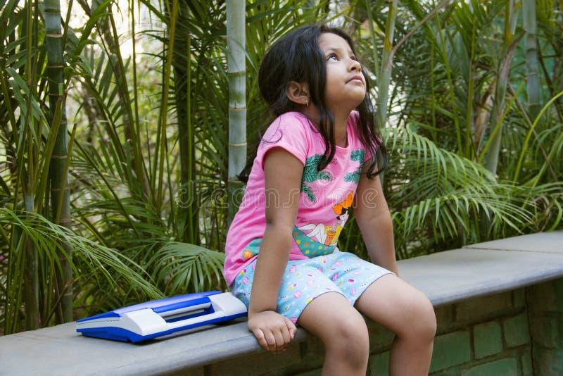Kleines indisches Mädchenumkippen, das aufwärts mit ihrem Spielzeuglaptop durch ihre Seite, Pune schaut lizenzfreies stockfoto