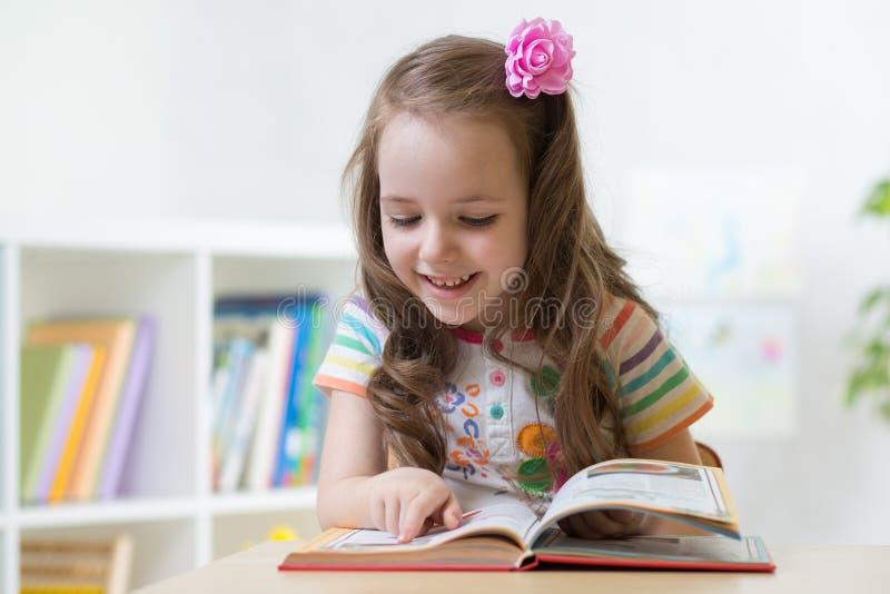 Kleines intelligentes Mädchen, das Buch beim Sitzen auf Stuhl in der Kindertagesstätte betrachtet stockfotografie