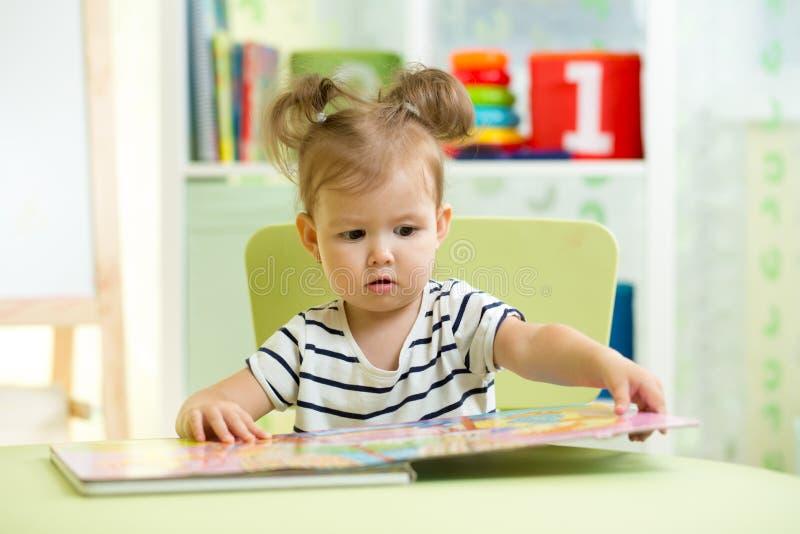 Kleines intelligentes Mädchen, das Buch beim Sitzen auf Stuhl in der Kindertagesstätte betrachtet lizenzfreies stockbild