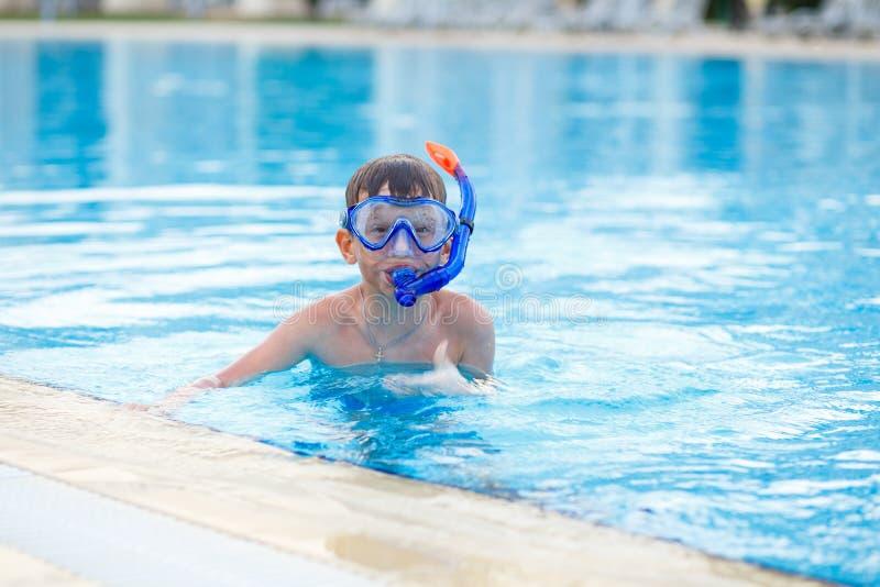 Kleines Jungentraining, das im Swimmingpool schnorchelt stockfotos