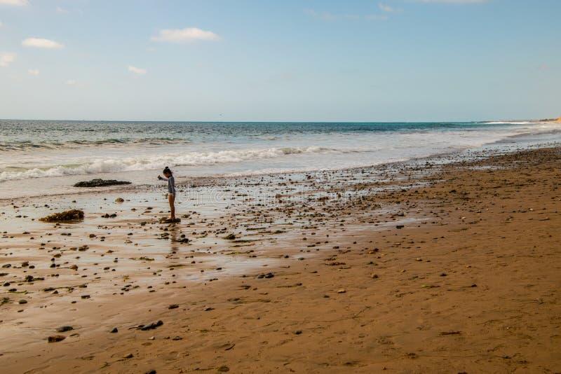 Kleines junges Mädchen steht auf einem Felsen auf einem abgelegenen felsigen Strand durch den Ozean stockfotos