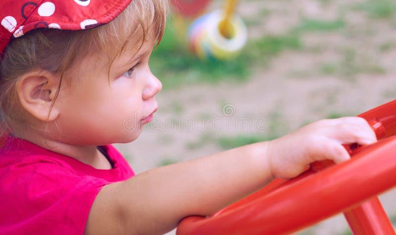 Kleines kaukasisches Baby sitzt am Steuer von einem Spielzeugauto Spielen auf dem Spielplatzkonzept lizenzfreie stockfotos