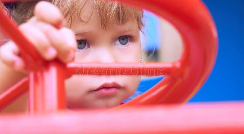 Kleines kaukasisches Baby sitzt am Steuer von einem Spielzeugauto Spielen auf dem Spielplatzkonzept stockbilder