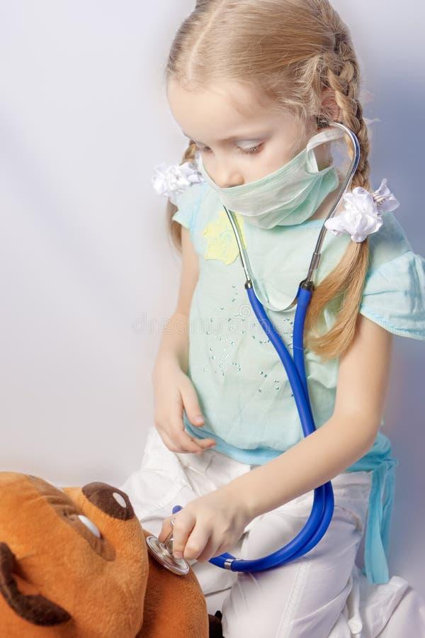 Kleines kaukasisches blondes Mädchen, das Spielzeugbehandlung bildet stockfotografie