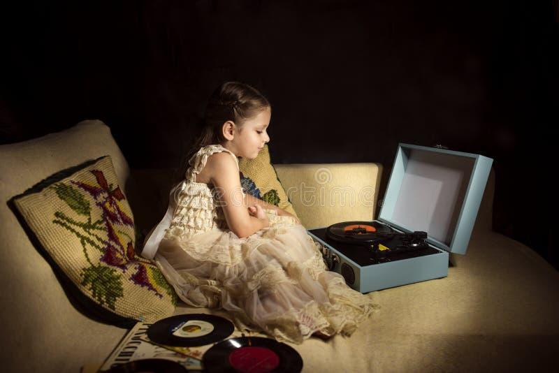 Kleines kaukasisches hörendes Mädchen eine Plattenspieleraufzeichnung lizenzfreies stockfoto