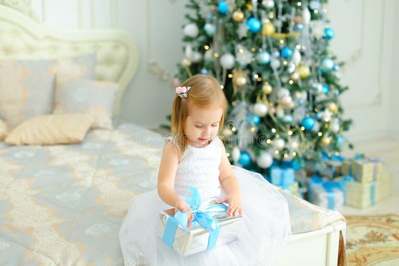 Kleines kaukasisches Mädchen, das auf Bett mit Geschenk sitzen und tragendes weißes Kleid, verzierter Tannenbaum im Hintergrund lizenzfreies stockbild