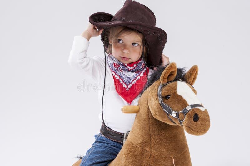 Kleines kaukasisches Mädchen in der Cowgirl-Kleidung, die auf symbolischem Pferd gegen Weiß aufwirft Halten von ihrem Stetson stockfotos