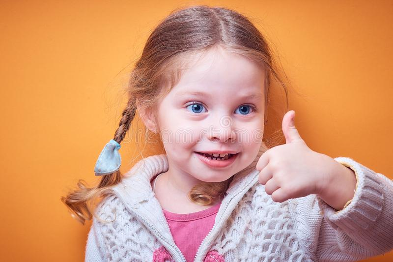 Kleines kaukasisches Mädchen zeigt anerkennend Daumen oben auf farbigem Hintergrund, Platz für Text lizenzfreies stockbild