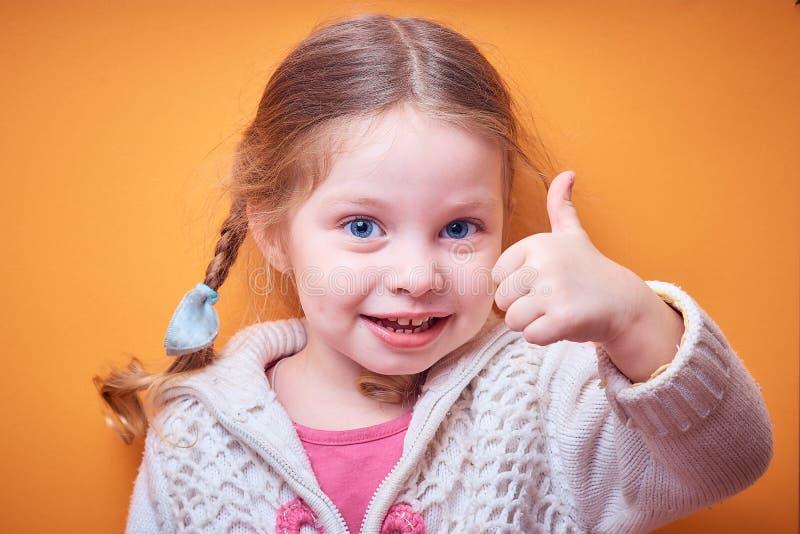 Kleines kaukasisches Mädchen zeigt anerkennend Daumen oben auf farbigem Hintergrund, Platz für Text stockbild