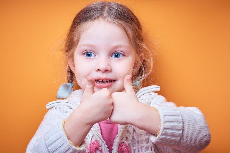 Kleines kaukasisches Mädchen zeigt anerkennend Daumen oben auf farbigem Hintergrund, Platz für Text lizenzfreie stockfotografie