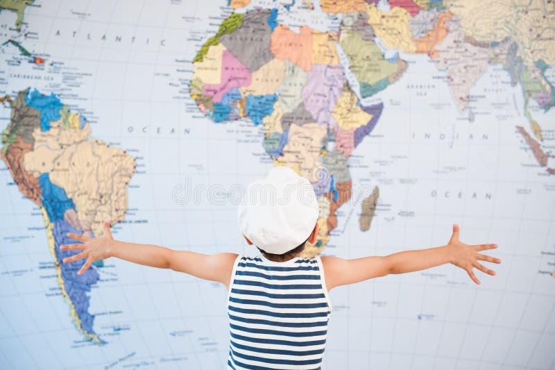 Kleines Kind in ausgebreiteten Händen Kapitänhutes zur Weltkarte vor Reise stockbilder