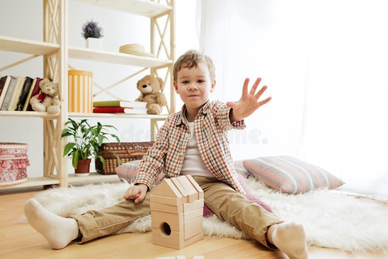 Kleines Kind, das auf dem Fußboden sitzt Hübscher Junge, der zu Hause mit hölzernen Würfeln palying ist lizenzfreies stockfoto