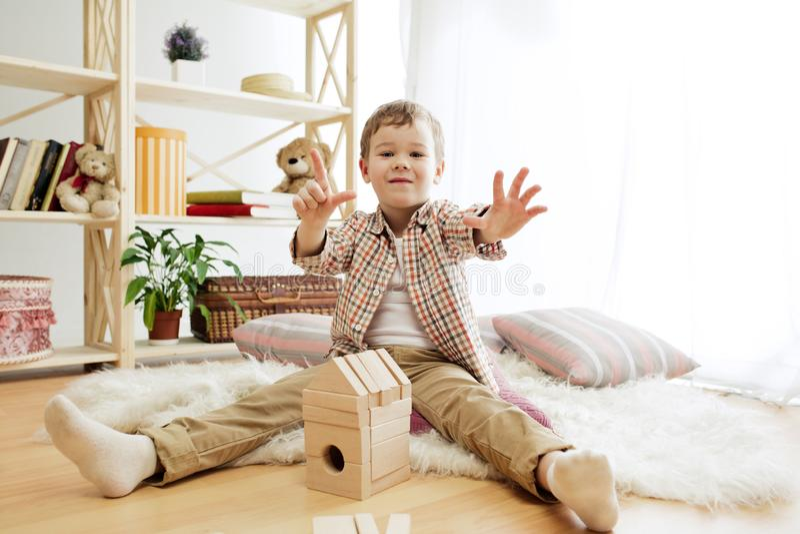 Kleines Kind, das auf dem Fußboden sitzt Hübscher Junge, der zu Hause mit hölzernen Würfeln palying ist stockfoto