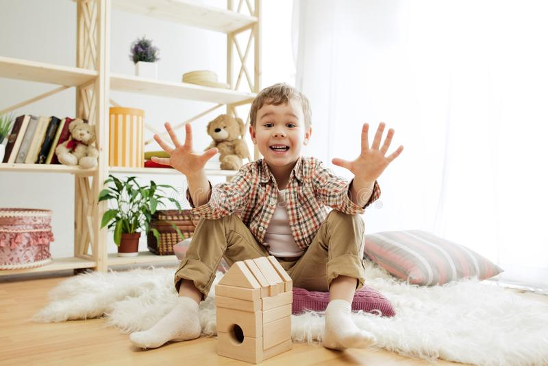 Kleines Kind, das auf dem Fußboden sitzt Hübscher Junge, der zu Hause mit hölzernen Würfeln palying ist lizenzfreie stockfotos
