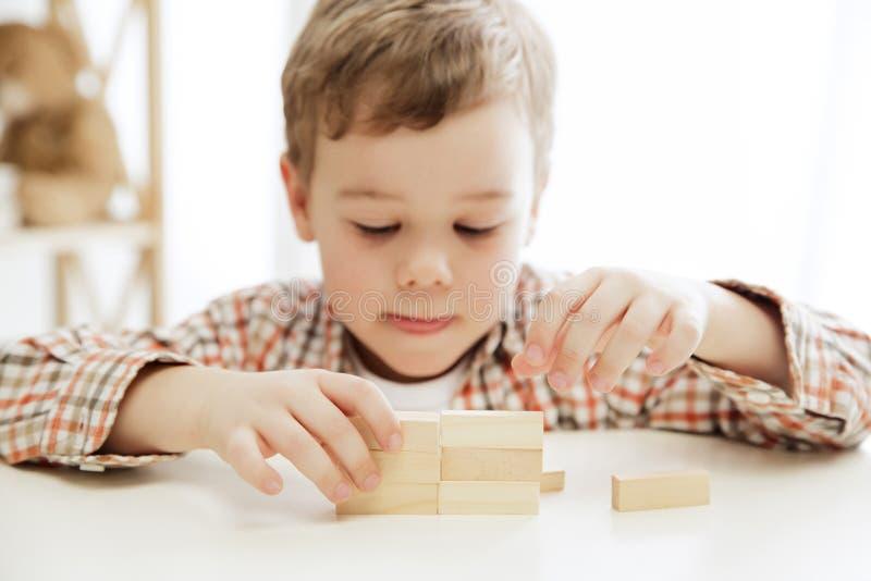 Kleines Kind, das auf dem Fußboden sitzt Hübscher Junge, der zu Hause mit hölzernen Würfeln palying ist lizenzfreie stockbilder