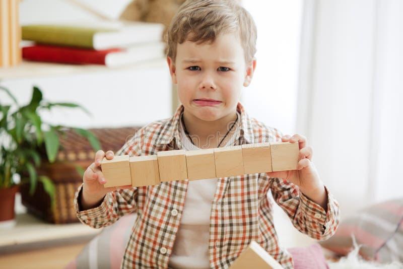 Kleines Kind, das auf dem Fußboden sitzt Hübscher Junge, der zu Hause mit hölzernen Würfeln palying ist lizenzfreies stockbild