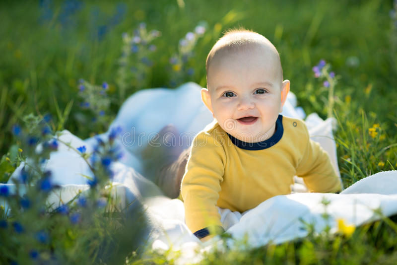 Kleines Kind, das auf einer Windel das Gras liegt lizenzfreies stockbild