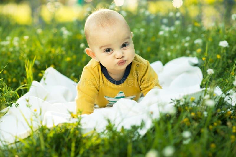 Kleines Kind, das auf einer Windel das Gras liegt lizenzfreie stockfotos