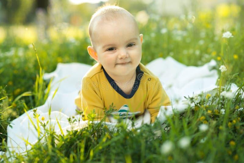 Kleines Kind, das auf einer Windel das Gras liegt stockfotos