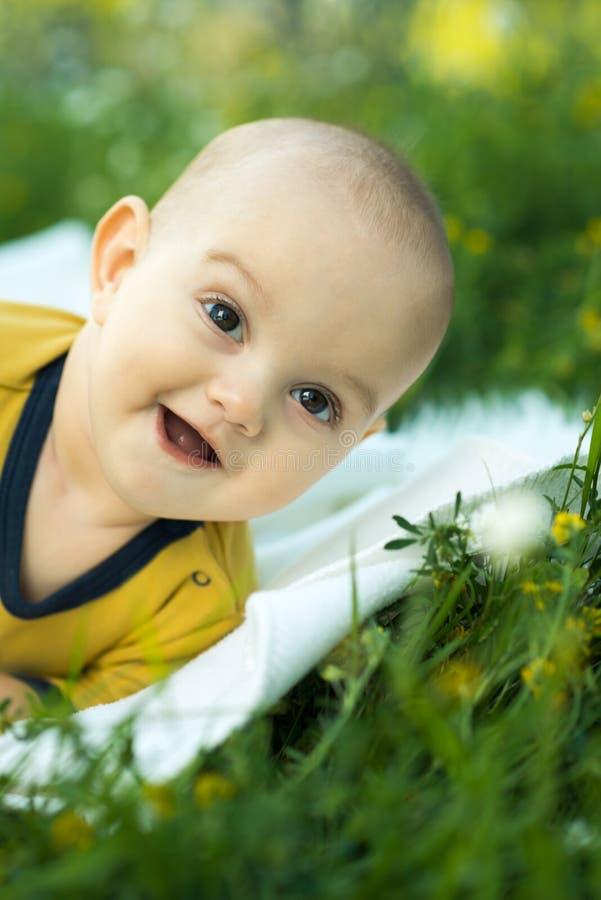 Kleines Kind, das auf einer Windel das Gras liegt lizenzfreies stockfoto