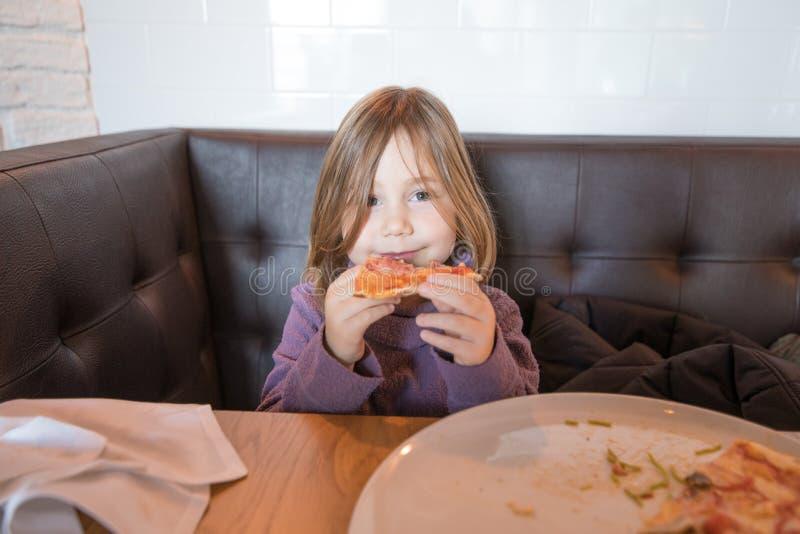 Kleines Kind, das betrachtet und Pizza im Restaurant isst lizenzfreie stockfotos