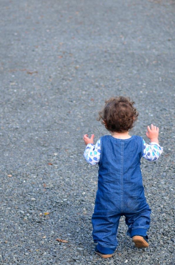 Kleines Kind, das gerade beginnt, zu gehen der erste Schritt stockfoto