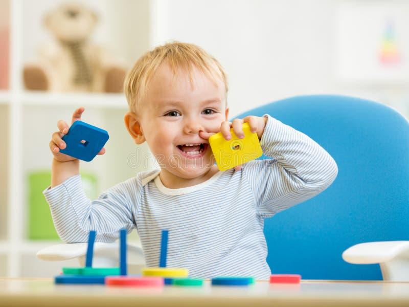 Kleines Kind, das mit Bausteinen spielt lizenzfreie stockfotos